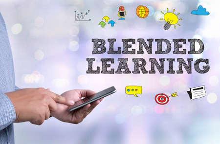 BLENDED LEARNING person holding a smartphone on blurred cityscape background Standard-Bild