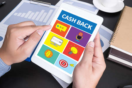 demonstrated: CASH BACK Modern people doing business, graphs and charts being demonstrated on the screen of a touch-pad,blank screen copy space Stock Photo