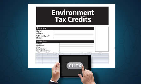 rebates: Environment Tax Credits Document Form Credits, on the tablet pc screen held by businessman hands - online, top view