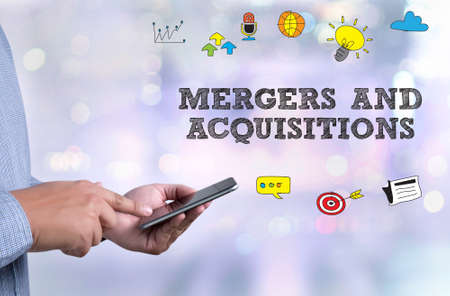 company merger: M&A (MERGERS AND ACQUISITIONS) person holding a smartphone on blurred cityscape background