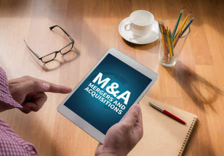 mergers: M&A (MERGERS AND ACQUISITIONS) touch digital tablet, coffee Stock Photo
