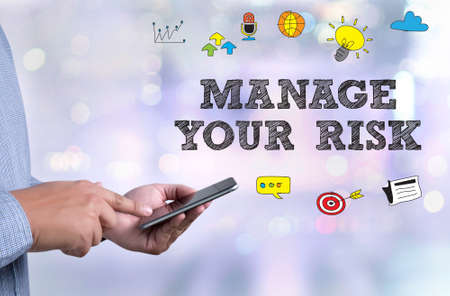 MANAGE YOUR RISK person holding a smartphone on blurred cityscape background Stock Photo