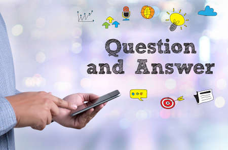 qa: Q&A - Question and Answer person holding a smartphone on blurred cityscape background Stock Photo