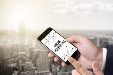 interstitial: ONLINE ADVERTISING person holding a smartphone on blurred cityscape background