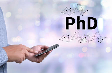 PhD Doctor of Philosophy Degree Education Graduation person holding a smartphone on blurred cityscape background Stock Photo