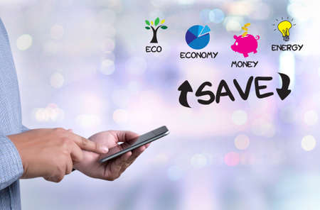 SAVE  Energy and Environmental and save investment person holding a smartphone on blurred cityscape background Stock Photo