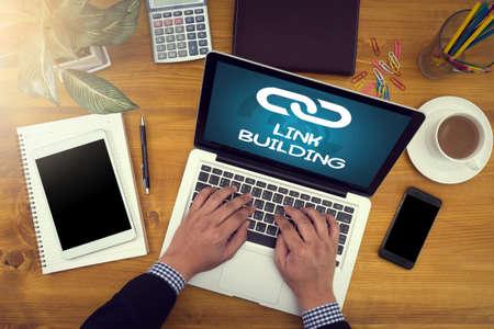 LINK BUILDING L'identité d'entreprise se moque d'un bureau de bois dur avec un ordinateur portable, une tablette, un smartphone et une tasse de café, homme travaillant Banque d'images