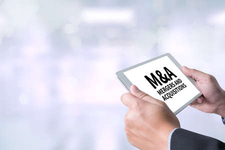 mergers: M&A (MERGERS AND ACQUISITIONS) Businessman holding a tablet computer on blurred city background