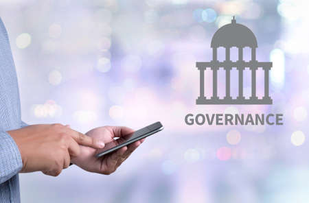 participatory: GOVERNANCE and Government building, Authority Government  person holding a smartphone on blurred cityscape background