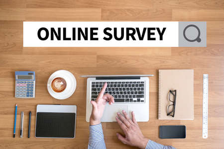 appraise: ONLINE SURVEY Businessman working with financial reports and a laptop with other objects around, coffee,  top view