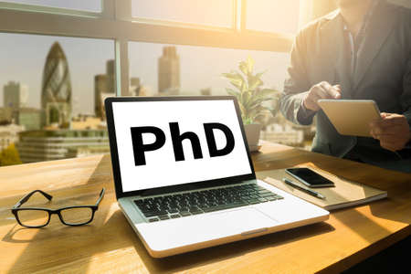 funding of science: PhD Doctor of Philosophy Degree Education Graduation Thoughtful male person looking to the digital tablet screen, laptop screen,Silhouette and filter sun Stock Photo