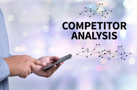 COMPETITOR ANALYSIS person holding a smartphone on blurred cityscape background