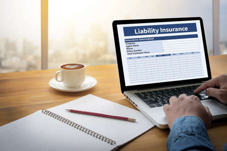 liability insurance: Form Document  Liability Insurance Money RIsk  Computing Computer  flare sun, Cropped image male freelancer sitting at the table Stock Photo