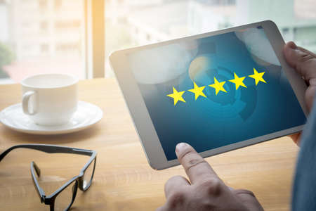 best rated: Businessman holding five star rating,Review, increase rating or ranking, evaluation and classification concept Stock Photo