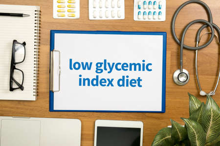 low glycemic index diet Professional doctor use computer and medical equipment all around, desktop top view Stock Photo