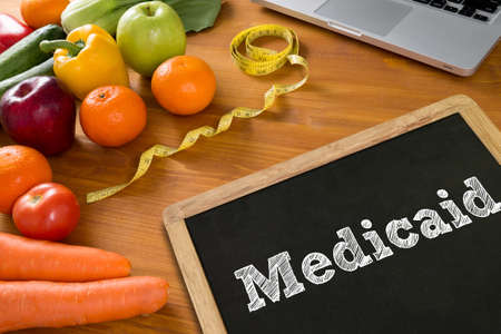 medicaid: Medical insurance and Medicaid and stethoscope.  fruit and tape measure on a wooden table, top view