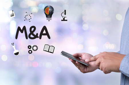 mergers: M&A (MERGERS AND ACQUISITIONS)  , Businessman working at office M&A Stock Photo