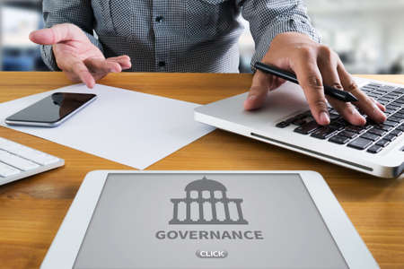 gov: GOVERNANCE and  building, Authority   Computing Computer  Laptop with screen on table Silhouette and filter sun Stock Photo