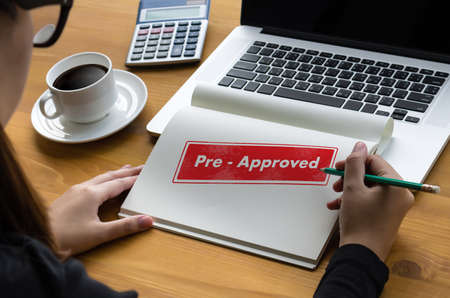 Woman preparing to sign the pre-approved letter on table Stock Photo