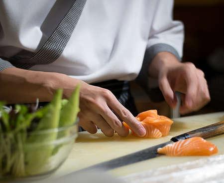 호텔이나 레스토랑에서 요리사 일본 요리 요리사, 손만 요리사. 그는 초밥을 먹고있다.