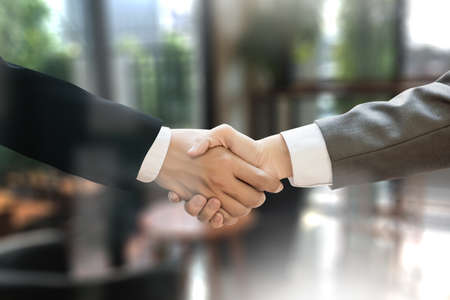 acquiring: M&A (MERGERS AND ACQUISITIONS) , Businessman handshake working at office M&A