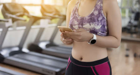 woman use phone  fitness exercise in gym smart gadgets and sport applications