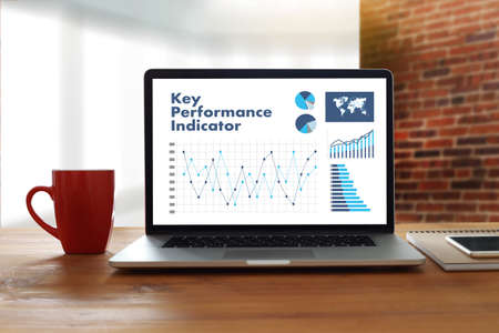 review: KPI acronym (Key Performance Indicator) Business team hands at work with financial reports and a laptop