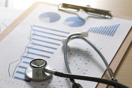 金融レポートのグラフと電卓医療レポートと聴診器
