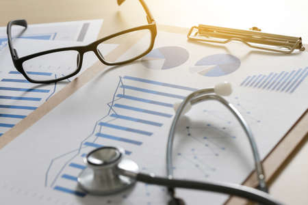 financial report chart and calculator Medical Report and stethoscope Archivio Fotografico