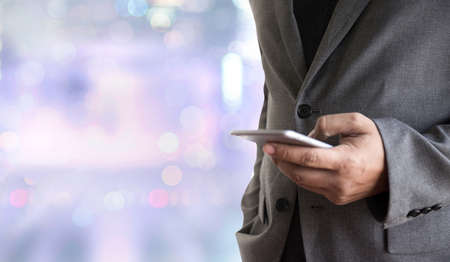 communication cartoon: person holding a smartphone on blurred cityscape background