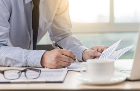 Ein Geschäftsmann, der die Finanzdiagramme liest, dokumentiert, um den Erfolg eines Arbeitsplans zu analysieren Standard-Bild