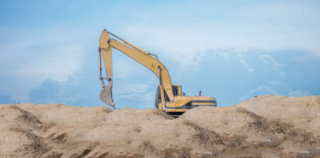A man working at the construction site on the  excavator for earthmoving