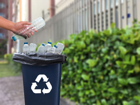 Mans hand putting plastic reuse for recycling concept environmental protection world recycle Zdjęcie Seryjne