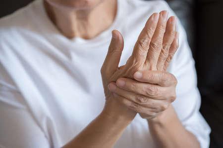 Oudere vrouw die lijdt aan pijn door reumatoïde artritis Stockfoto