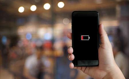 Schließen Sie herauf Mannhände unter Verwendung des niedrigen geladenen Batterieschirms der intelligenten Telefonbatterie
