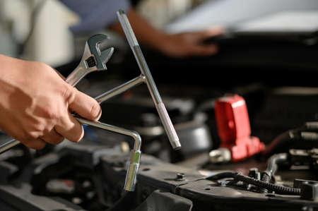 Reparaturservice Auto Automechaniker, der in der Garage arbeitet Automechaniker mit Schraubenschlüssel in der Garage