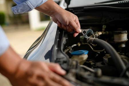 Servicio de reparación de automóviles Mecánico de automóviles que trabaja en el garaje Mecánico de automóviles con llave en el garaje Foto de archivo