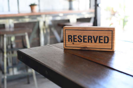 Restaurant reserved table sign Reserved Table. A tag of reservation placed on the wood table Foto de archivo