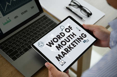 WORD OF MOUTH MARKETING Business team hands at work with financial reports and a laptop