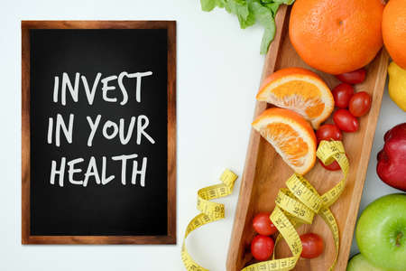 Invest in your health , Healthy lifestyle concept with diet and fitness , Get fit in  , fitness equipment and healthy food Foto de archivo - 130552028