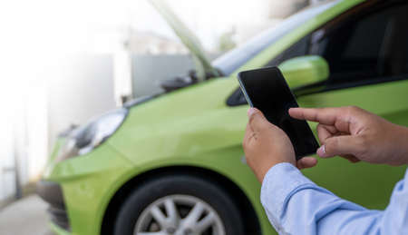 man Using a mobile phone call to  assistance Help with a broken down car assist stop car roadside breakdown Stock Photo