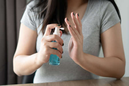 Woman cleaning her hands sanitizer virus and prevent covid-19 virus spraying alcohol gel or antibacterial