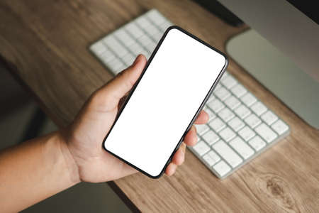 Top view Mockup image hand using a smartphone man Holding Cell Phone With Blank Screen