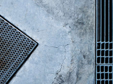Steel grate of manhole cover duty drain on the concrete roadside. Stock Photo