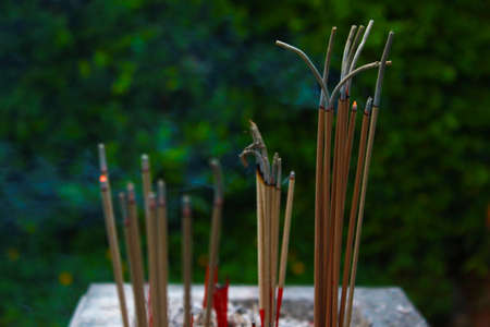 Incense sticks in ashes bucket photo