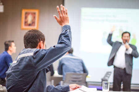 college education: Students lifting hands in college class with teacher Stock Photo
