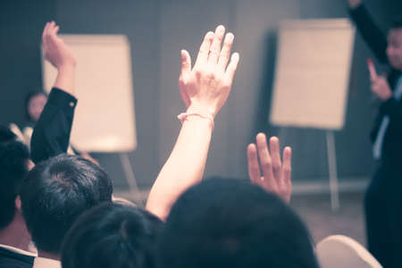 lifting hands: Students lifting hands in college class with teacher Stock Photo