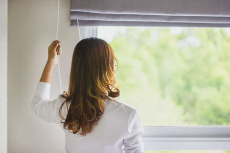 aspirational: Rear view of a young woman wearing a robe and holding the curtains open to look out of a large light window at home, interior. Positive and aspirational lifestyle. Woman looking out a window, indoors. Stock Photo