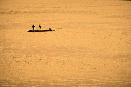 Fishermen in boat on morning sunrise
