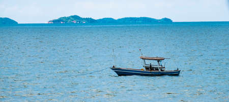 Fishing boats are overwhelmingly in the midst of the sea on a beautiful blue sky. Banco de Imagens